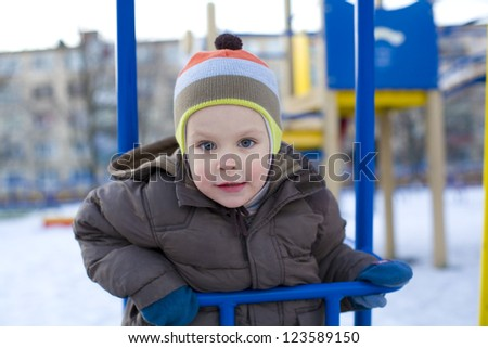 Small child riding on swing in winter - stock photo