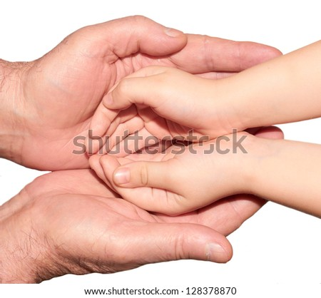 Small child's hand in the large  palms of an adult - stock photo