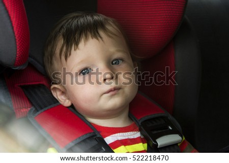 Small child sits in the automobile armchair, fastened by seat belts. Small child sits in the automobile armchair, fastened by seat belts. Small child sits in the automobile armchair