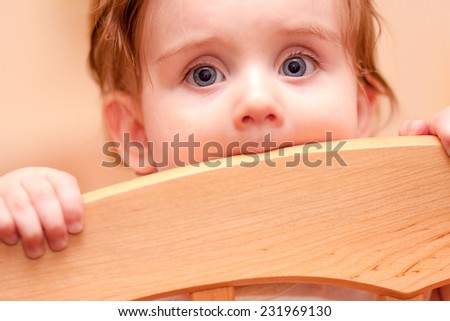 small child standing peeps out cot - stock photo
