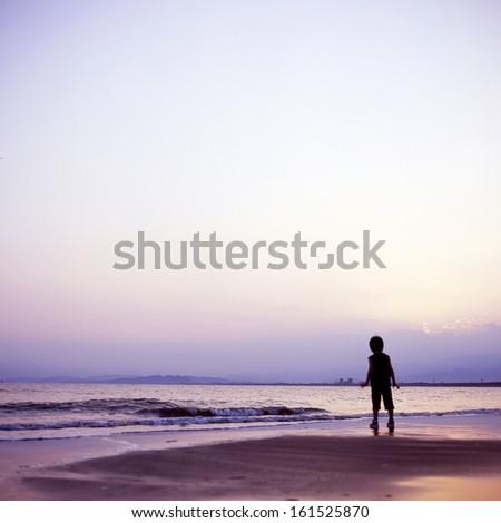 Small child walking on sandy beach near ocean. - stock photo
