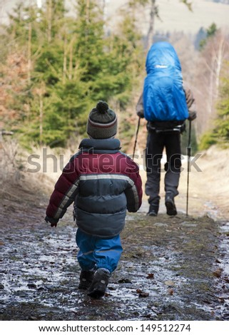 Small child walking or hiking through the forest behind his father. - stock photo