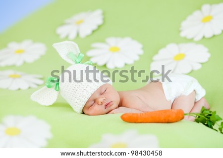 small child with a rabbit ears. Lying on his stomach with a carrot healthy food - stock photo