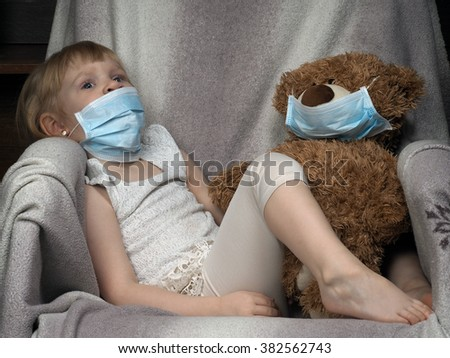 Small child with a toy bear cub in a medical mask. The girl is sad. Concept - an allergy to dust, wool, asthma. risk of infection, viruses