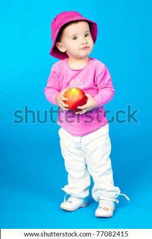 small child with an apple on a blue background - stock photo