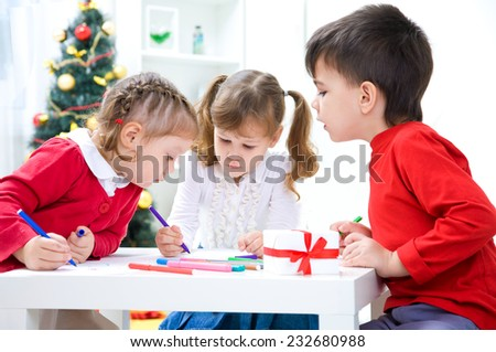 small children are sitting at the table and write a letter to Santa - stock photo