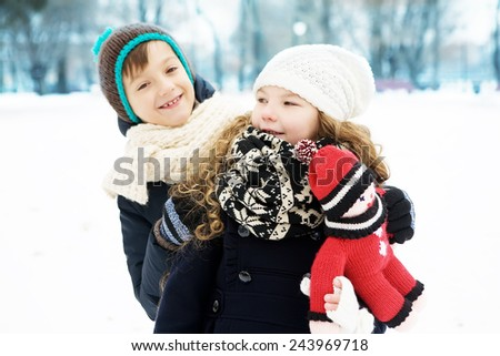 Small children boy and girl play together in a snowy winter park. In the warm cloth - stock photo