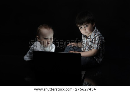 small children look into the computer - stock photo