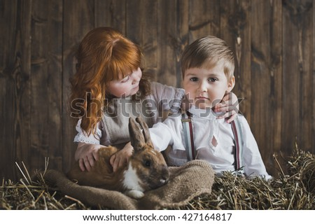 Small children play among the hay.