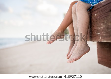 Small children sitting on the wooden pier in the water and enjoying summer day. Bare feet of boy and girl. Vacation by the sea. Outdoors. Siblings. Sister and brother by the ocean. - stock photo