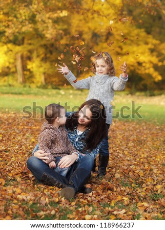 small children with mother playing in the park in autumn