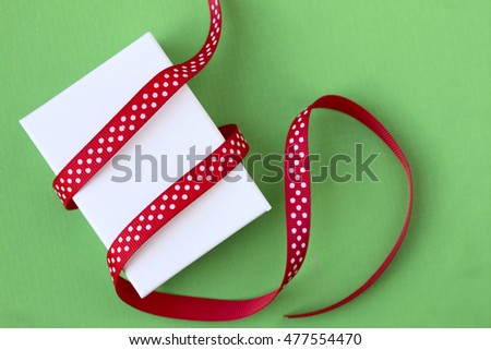 Small Christmas gift box and ribbon on green background