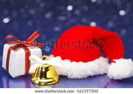Small Christmas present and Santa hat on white sparkle background. Christmas present, Santa hat and bell on snowing night background.  - stock photo