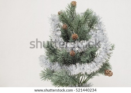 small christmas tree wiht fir cones decoreted with tinsel