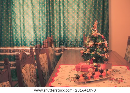 Small Christmas tree with decorations, gifts and citrus on the table