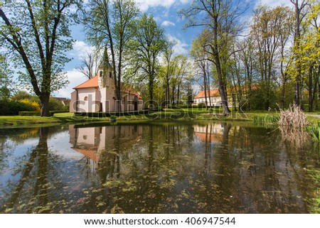 Small church is reflected on the surface of the pond in the park. Spring rural landscape. Miroslavske Kninice, South Moravia, Czech Republic - stock photo
