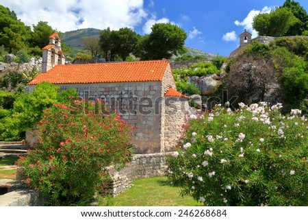 Small church surrounded by colorful flowers and Mediterranean vegetation, Montenegro - stock photo