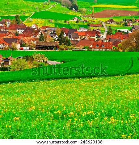 Small City High Up in the Swiss Alps Surrounded by Pastures  - stock photo