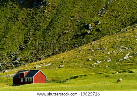 Small, classic, red Norwegian house over mountains, - stock photo