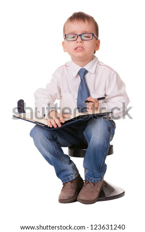 Small clever boy thinks his wishes to write them in notebook isolated on white background - stock photo
