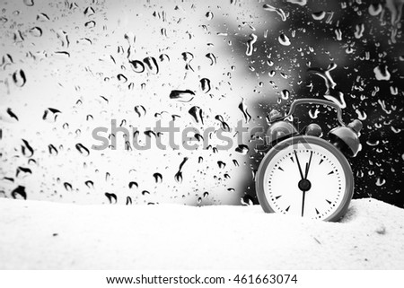 small clock on white sea sand with blur drop on mirror background