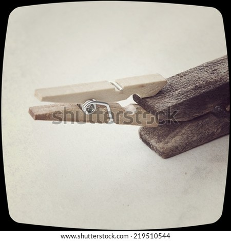 Small clothespin biting an old one on an isolated background and a vintage filter effect. - stock photo