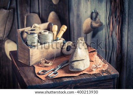 Small cobbler workplace with tools, shoes and laces - stock photo
