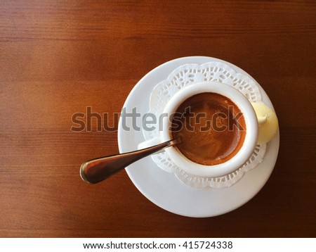 Small coffee cup with space on the old wooden table - stock photo