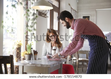 Small coffee shop owner serving coffee. - stock photo
