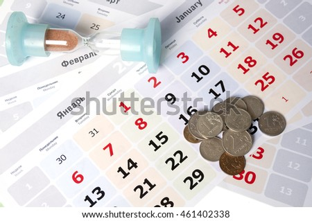 Small coins in a heap on the calendar and hourglass