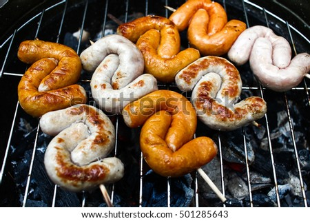 Small colorful s-shaped grilled sausages  on barbecue