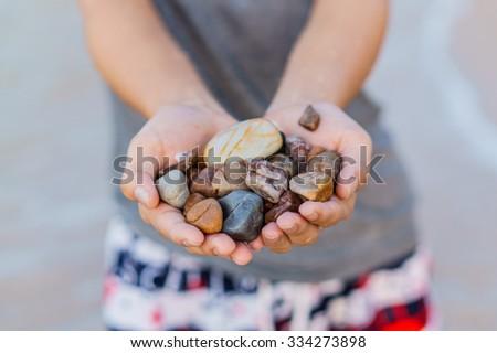 Small colorful stones in hand on sea coast blur - stock photo