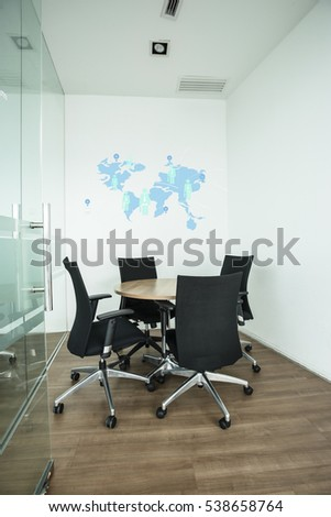 Small conference room in modern environment with windows, round table and armchairs with world map and business man icon