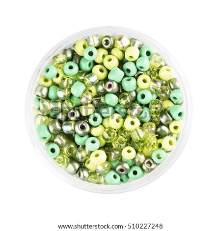 Small container of glass seed beads isolated on white background overhead view.