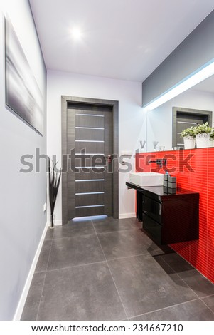 Small contemporary toilet with red tiles on the wall - stock photo