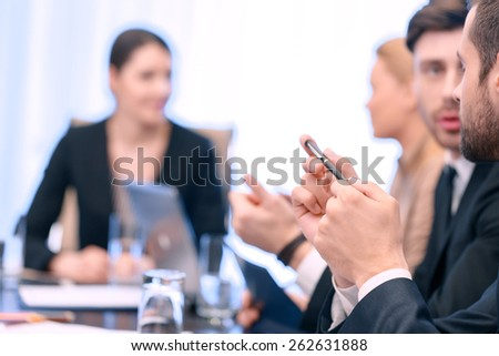 Small conversation at the meeting. Closeup of two male business partners communicating at the meeting with blurred background of other meeting participants - stock photo