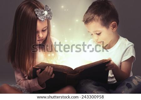 Small couple opened a magic book  - stock photo