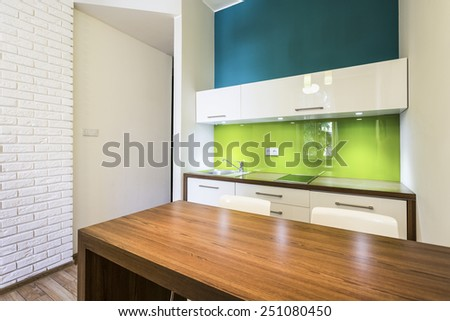 Small cozy kitchen interior with wooden table - stock photo