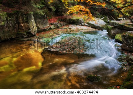 Small creek in rocky scenery of the mountain forest - stock photo