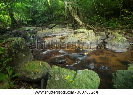 Small creek near waterfall with fast flowing water and rocks formation. - stock photo