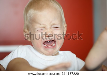 Small, crying and kicking toddler having a temper tantrum at home, defying parents. Childhood, developmental phase, hard parenthood concept.  - stock photo