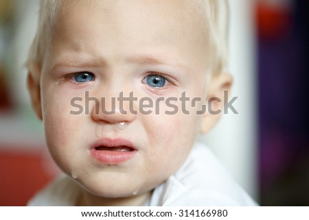 Small, crying toddler after a temper tantrum at home, defying parents. Childhood, developmental phase, hard parenthood concept.  - stock photo