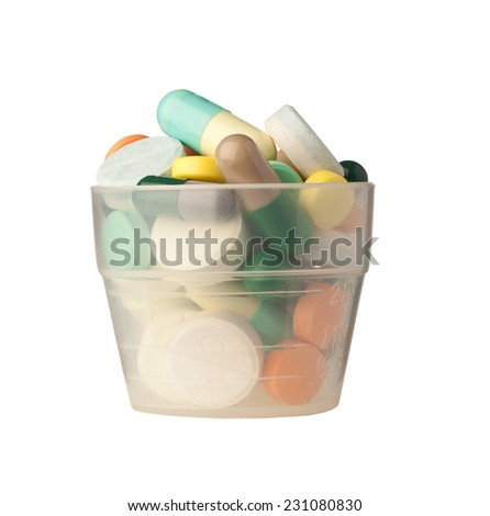 Small cup filled with pills and capsules isolated on white background  - stock photo