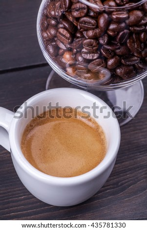 Small cup of coffee with a glass full of coffee beans on a wood table