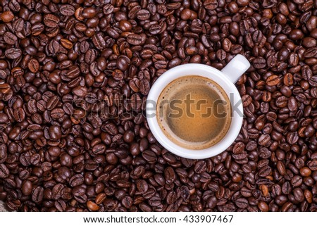 Small cup of espresso coffee on a pile of roasted coffee beans