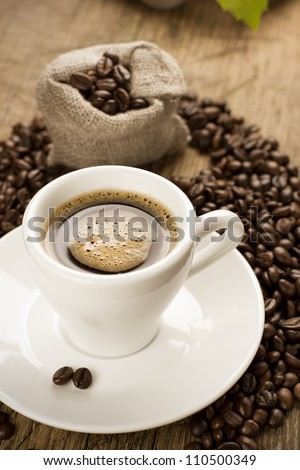 Small cup of strong coffee on a brown background with coffee beans