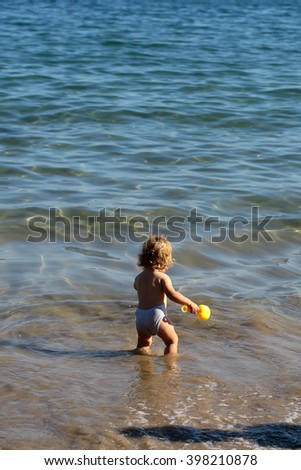 Small curious blonde child boy standing on sea coast beach with wavy water sunny twilight outdoor playing on natural background, vertical picture - stock photo