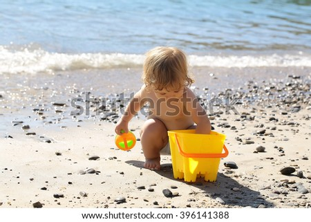 Small curious funny blonde child boy sitting on sea coast beach with wavy water sunny day outdoor playing with yellow plastic pail on natural background, horizontal picture - stock photo