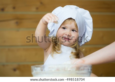 small cute baby boy or child with happy face in white cook uniform with chef hat and apron kneading dough with flour in glass bowl in kitchen on wooden or wood background with female hands
