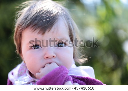 Small cute baby girl with pretty face and funny eyes outdoor on natural background closeup